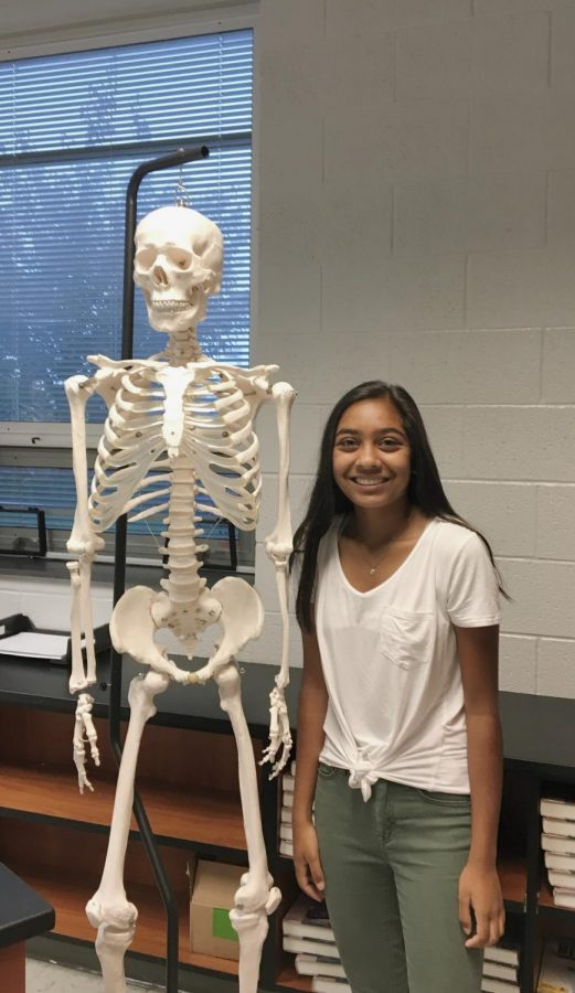 Leader of HOSA, Amani Patel poses next to a skeleton in Mr. Gould's room where much of the club's activities take place.