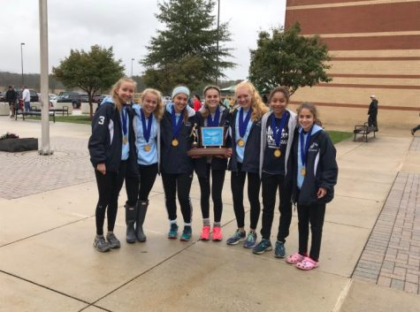 The girls pose with their trophy and medals under the rainy sky after the district meet. The team won first place, and many of the girls won individual medals as well.