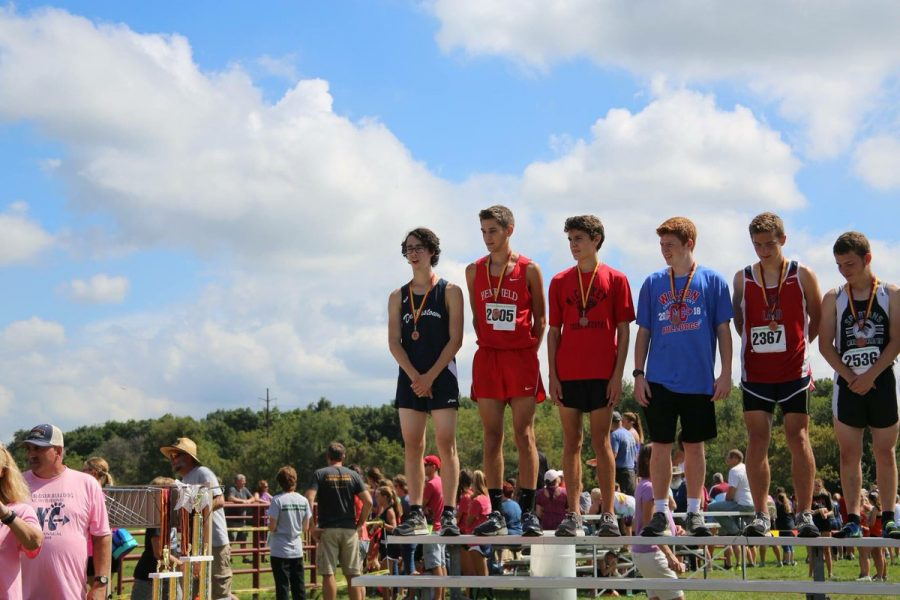Rory McCleary, one of the Boy's Cross Country key members, receiving his medal at the Big Springs race.