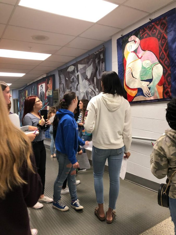Students take a break from class to admire different paintings from history and great painters.