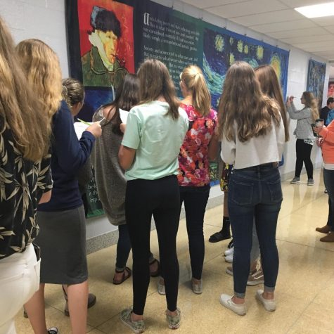 A group of female students are looking at the Starry Night by  Vincent Van Gogh at the exhibit in the art gallery.