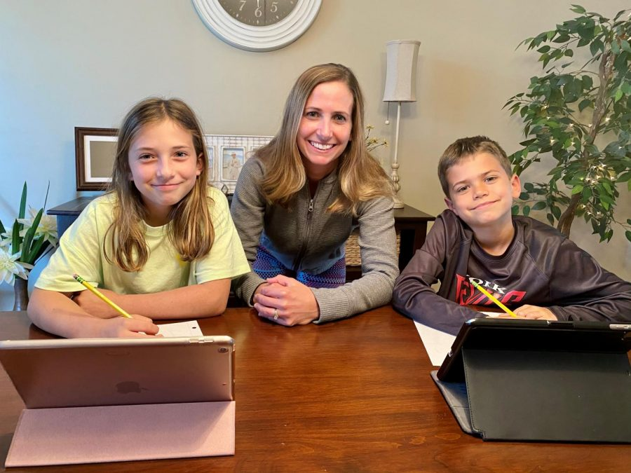 Myla, left, 11 years old, doing schoolwork with Mrs. Guttridge, middle, also with her brother, 8-year-old Grant.