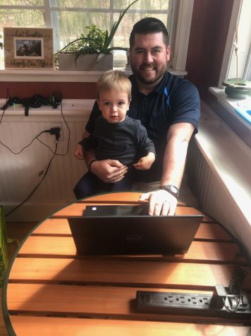 Mr. Zelger holding his 2-year-old son, Nathaniel, also typing on the laptop. It is seen that he is juggling, by having a child and doing Zoom classes.